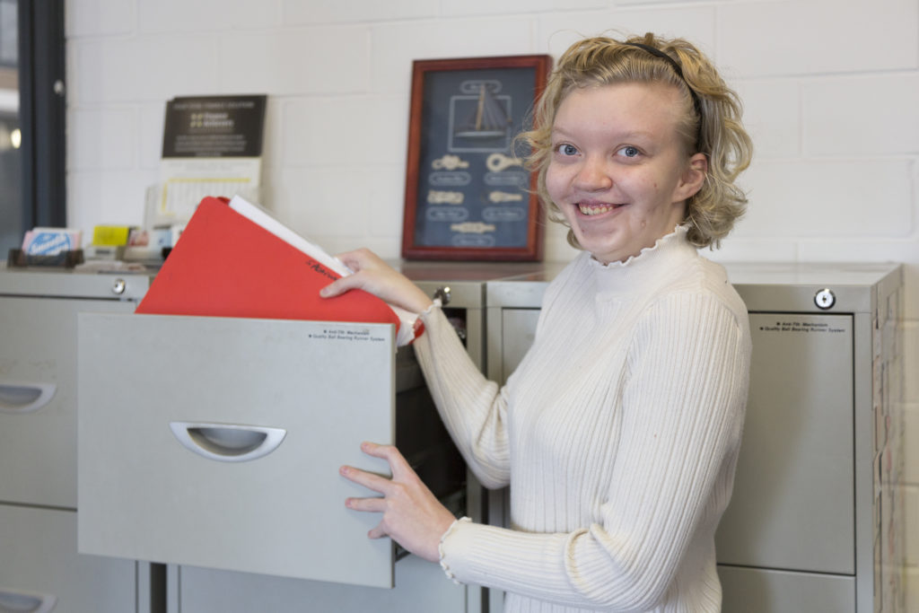 Tayla grabbing a file from a cabinet