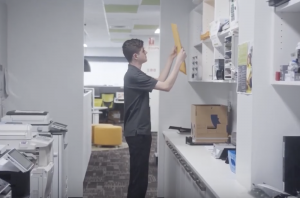 Man grabbing a file from a cupboard