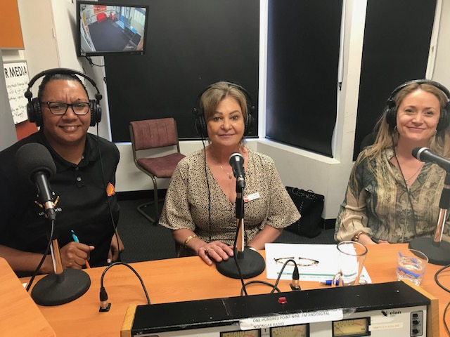 Three people smiling while on radio with headsets on