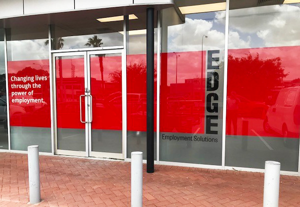 Shop front of the new Edge office. Branded with logos, red window and slogan- 'changing lives through the power of employment'