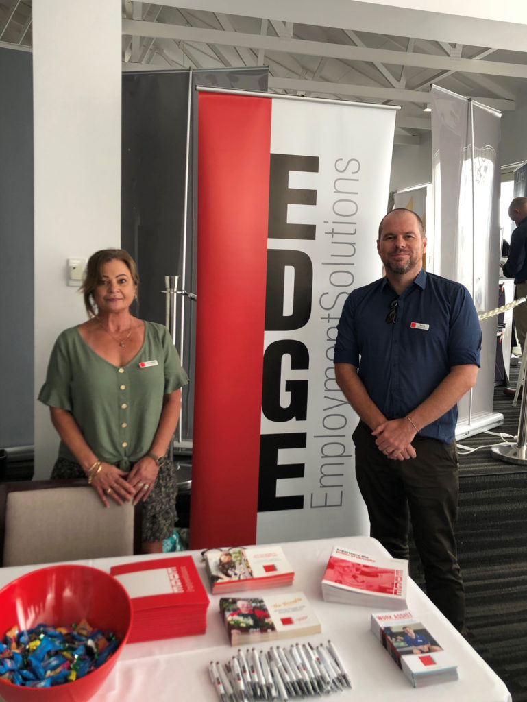 Two Edge staff standing in front of Edge banner and Edge booth.