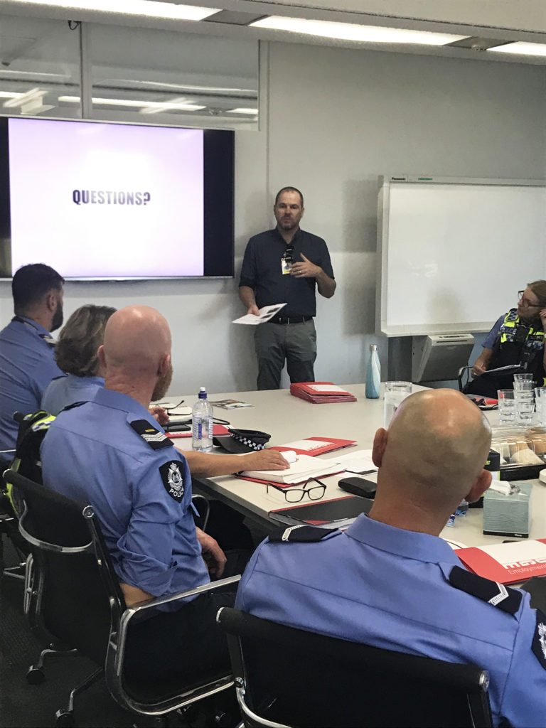 Man presenting to a group of police officers