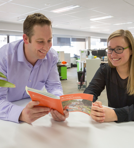 Man looking at a book while the woman next to him smiles for the camera