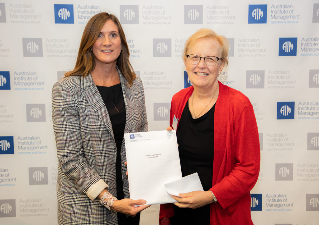 Two women standing together, both holding the grant document.