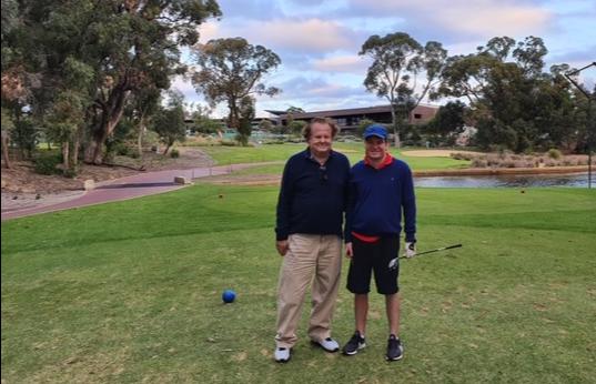 Alexendar standing beside a man on a golf green