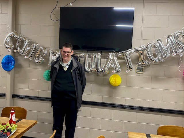 Man smiling while standing in front of balloons spelling out Congratulations!