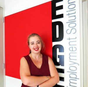 Edge's Communications Coordinator Ashton proudly standing in front of the Edge logo