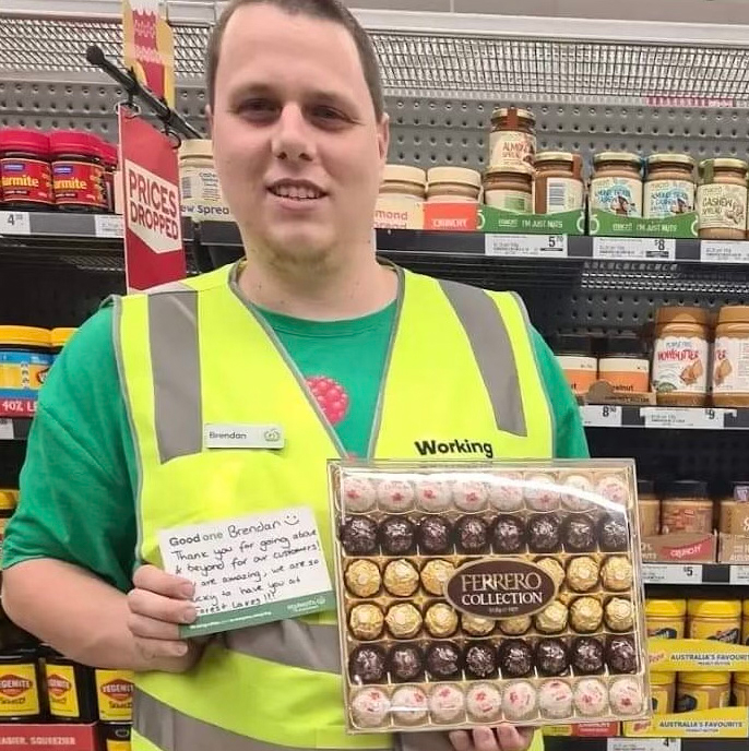 Brendan holding a box of chocolates and his 'Good One' form in an isle