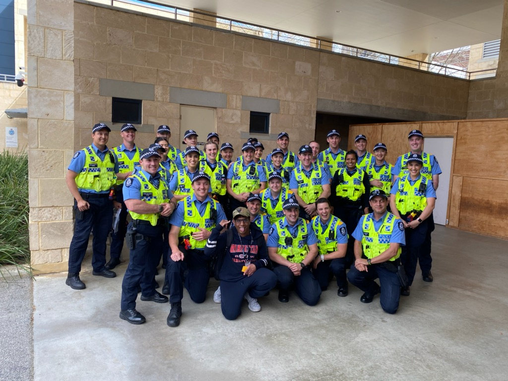 Ashveer smiling for a group photo for multiple police officers