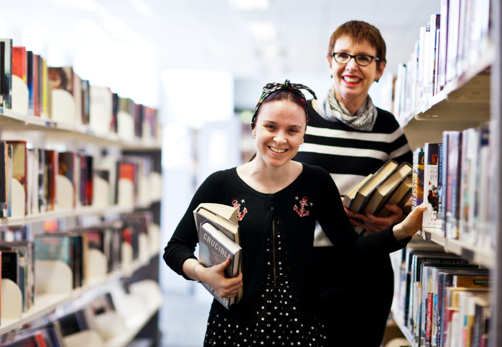 Jessica holding books while smiling and grabbing a book of the library shelf with a woman grabbing a book behind her