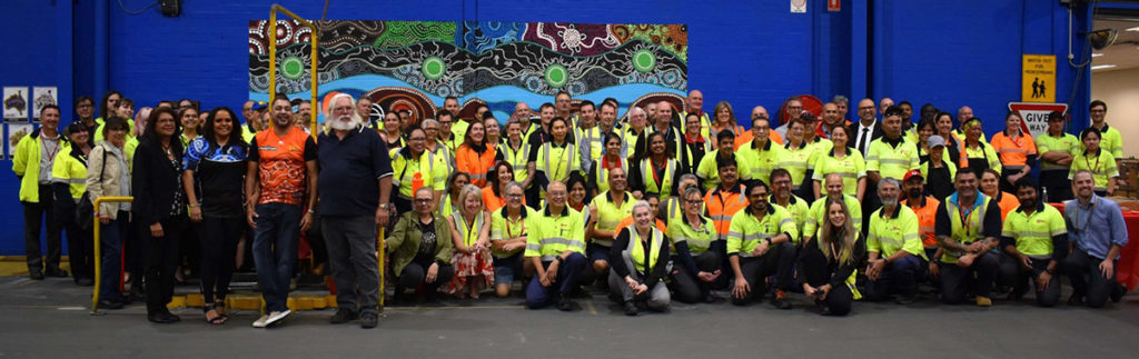 Perth Parcel Centre staff and guests with Bynder in front of the new mural