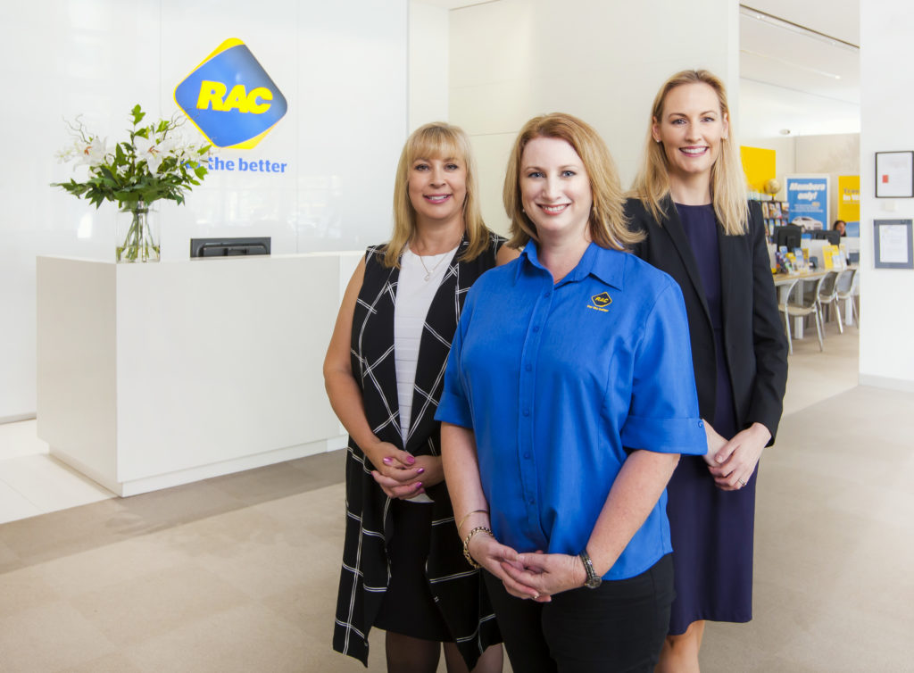 Image of three RAC staff standing in front of their reception desk
