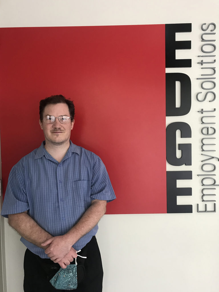Tristan smiling in front of the Edge sign