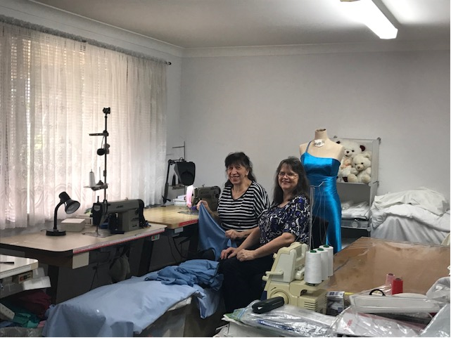 Two women sitting down beside material and cloth they use for work