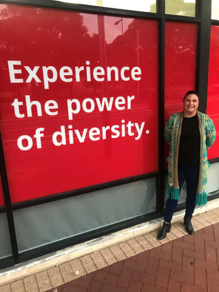 Natalie smiling in front of Edge labelled doors- experience the power of diversity,