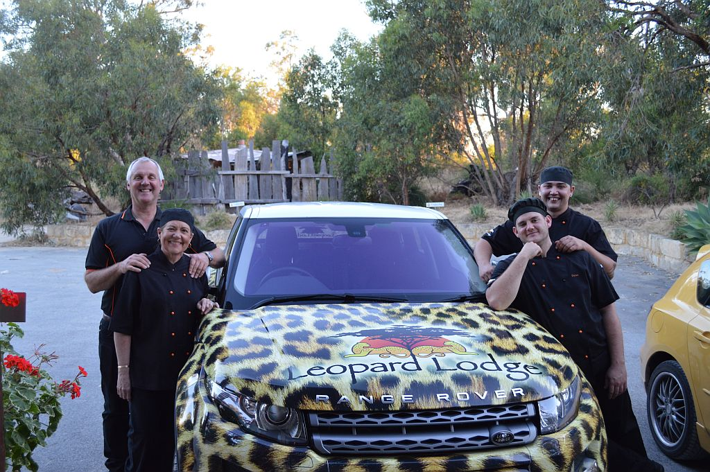 Four people standing either side of a branded Leopard Lodge car.